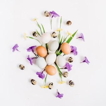 Braune und weiße ostereier, wachteleier, gelbe und lila blüten auf weißer oberfläche