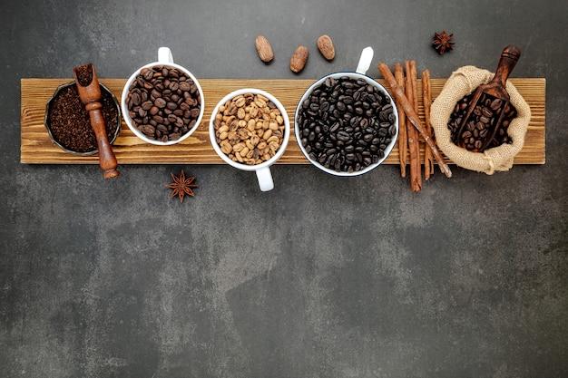 Braune ungeröstete und dunkel geröstete kaffeebohnen in einer kaffeetasse mit schaufeln auf dunklem stein.