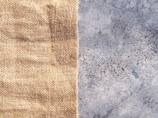 Braune webgewebe-stoffstruktur mit sackleinenhintergrund und beton