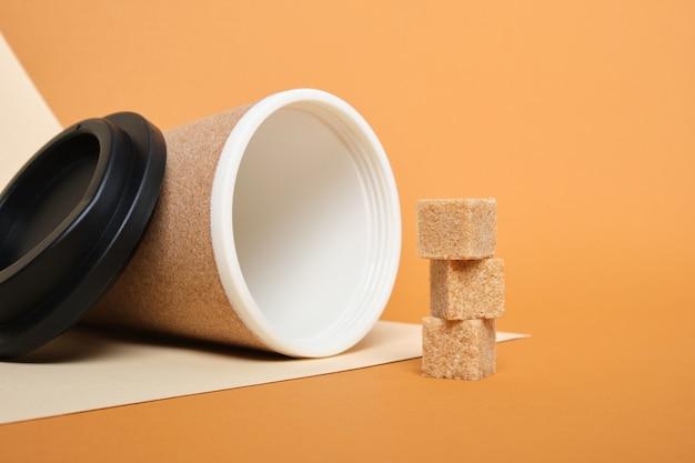 Braune zuckerwürfel und thermobecher aus kork auf einem beigen und braunen hintergrundkopierraum