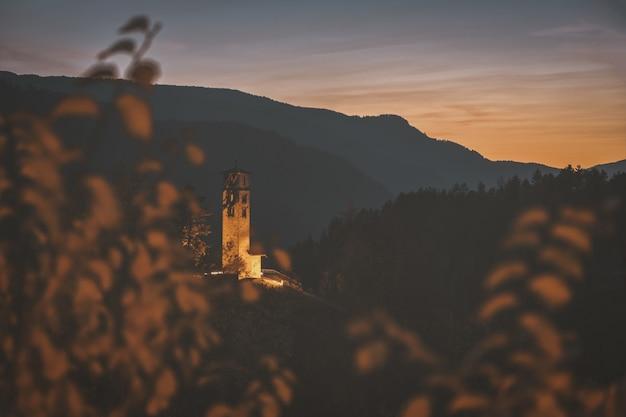 Brauner betonturm auf berg während der goldenen stunde