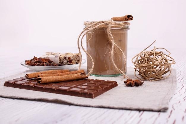 Brauner detox coctail mit zimtstangen und schokolade liegen auf dem tisch