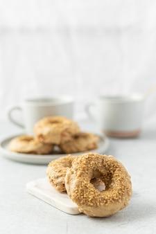 Brauner donut neben weißem keramikbecher auf weißem tisch