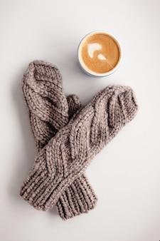 Brauner fäustling und becher mit cappuccino auf weißem holztisch