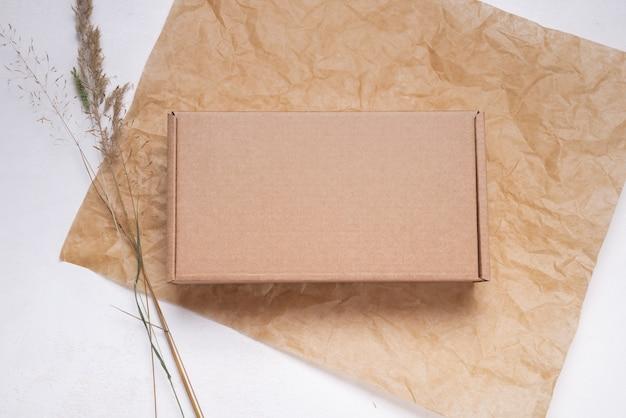 Brauner flacher karton mit getrockneten blättern verziert, ansicht von oben