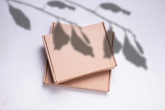 Brauner flacher karton, verziert mit schatten von baumblättern