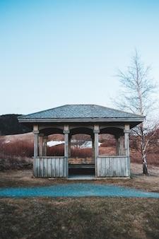 Brauner hölzerner pavillon nahe bäumen während des tages