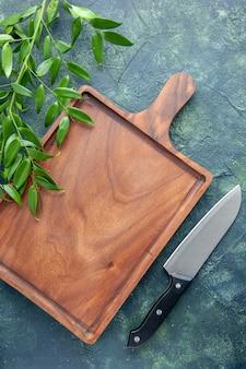 Brauner hölzerner schreibtisch der draufsicht auf einem dunklen blauen hintergrundmesser-lebensmittelfarbe fleischküche alte metzgerküche