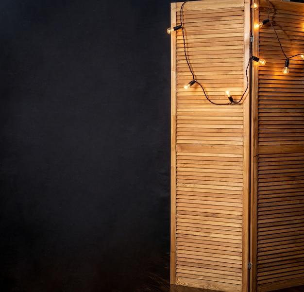 Brauner holzklappschirm mit glühbirnen gegen schwarze wand