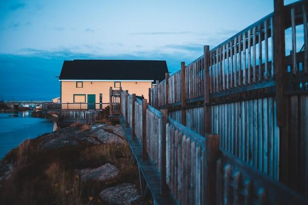 Brauner holzzaun nahe braunen holzhäusern unter blauem himmel während des tages