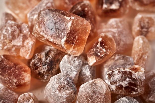Brauner karamellisierter klumpenrohrzuckerwürfel selektiver fokusmakronahrungsmittelhintergrund