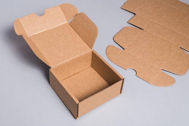 Brauner karton auf grauem hintergrund, geöffnet, innen leer