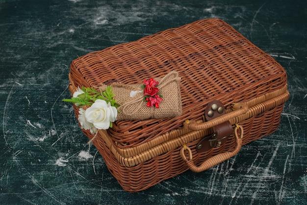 Brauner koffer mit winzigem blumenstrauß auf marmortisch.