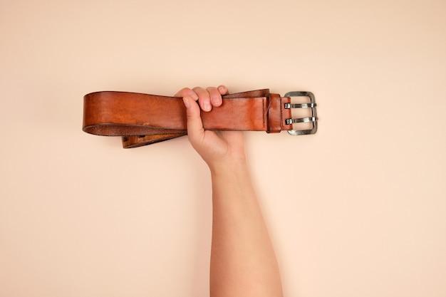 Brauner ledergürtel in weiblicher hand