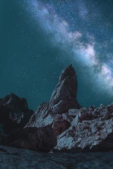 Brauner monolith unter blaugrüner und grauer milchstraße