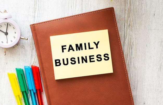 Brauner notizblock, aufkleber mit der aufschrift family business, farbige stifte, uhr auf einem holztisch. geschäftskonzept.