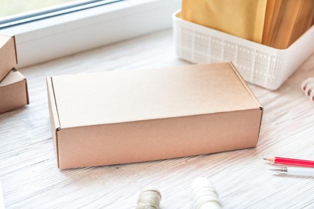 Brauner postkarton auf hölzernem schreibtisch, arbeitsbereich