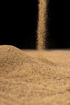 Brauner sand fällt auf schwarze wand