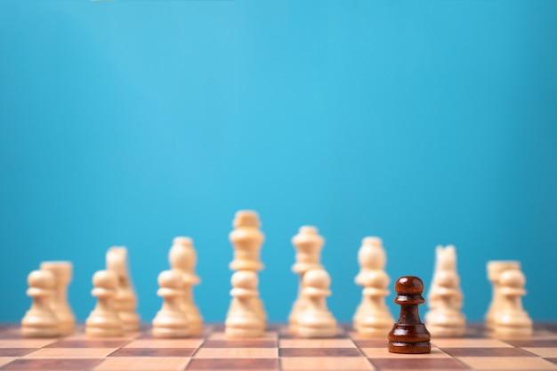 Brauner schachmann, der vor weißem schach steht, konzept der herausforderung im wettbewerb