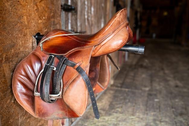 Brauner schäbiger ledersattel mit schwarzen zügeln, die an einer stahlstange hängen, die aus der wand im stall herausragt