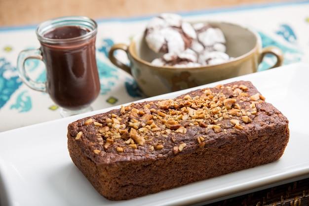 Brauner schokoladenkuchen und kastanien mit heißer schokolade und keksen