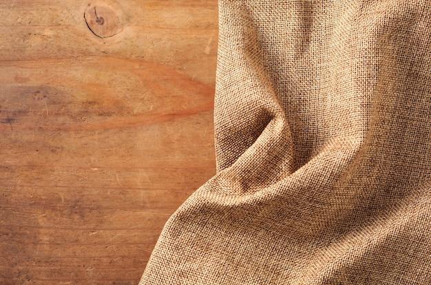 Brauner stoff auf hölzernen hintergrund