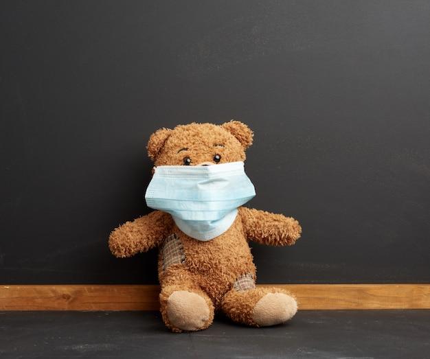 Brauner teddybär, der in einer medizinischen einwegmaske auf einem schwarzen tafelraum sitzt