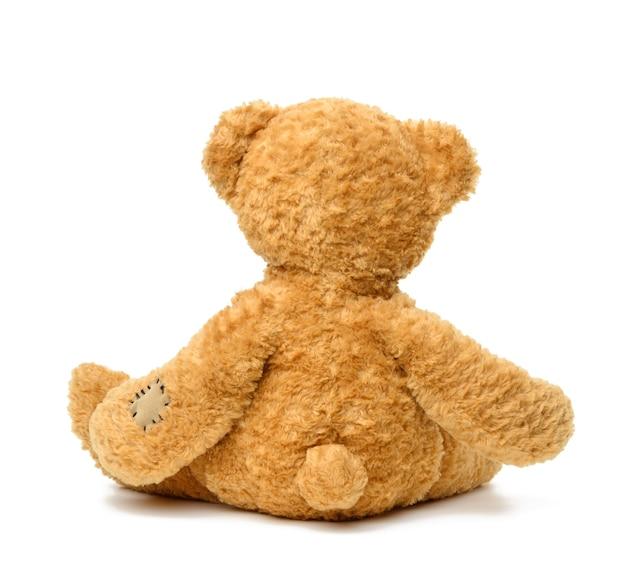 Brauner teddybär, der zurück auf weißem lokalisiertem hintergrund sitzt, spielzeug mit flecken