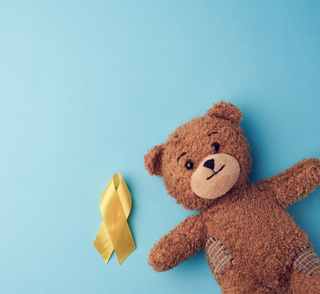 Brauner teddybär hält in seiner pfote ein gelbes band, das in einer schleife auf einem blauen hintergrund gefaltet ist. konzept des kampfes gegen krebs bei kindern