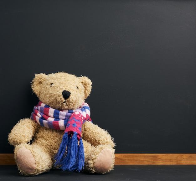 Brauner teddybär in einem gestrickten schal, der auf einem raum der schwarzen kreidetafel sitzt