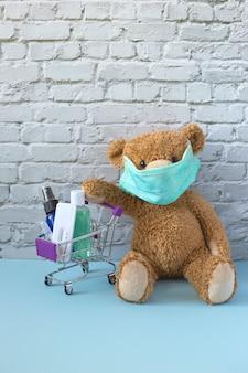 Brauner teddybär in medizinischer maske sitzt und hält seine pfote auf einem kleinen einkaufswagen mit alkoholgel, antibakteriellem handspray und coronavirus-test