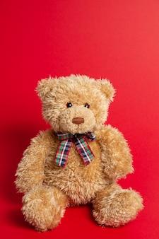 Brauner teddybär lokalisiert auf rotem hintergrund