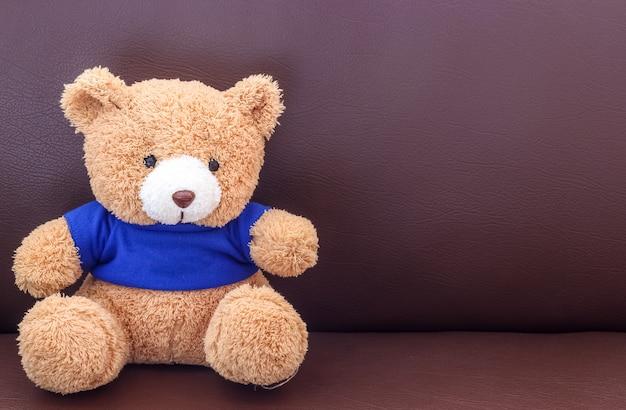 Brauner teddybär mit blauem hemd auf dem sofa
