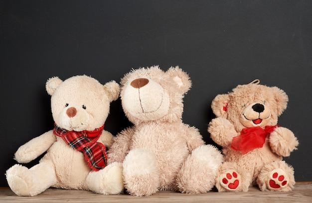 Brauner teddybär sitzt auf einem braunen holztisch hinter einer leeren schwarzen kreidetafel
