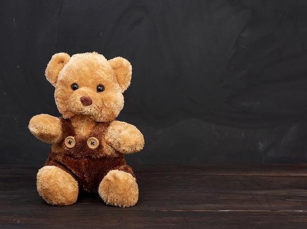 Brauner teddybär sitzt auf einem braunen holztisch