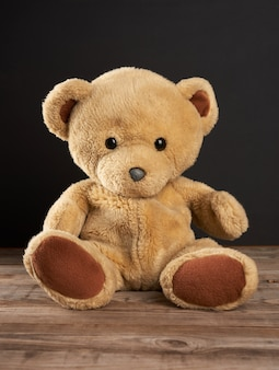 Brauner teddybär sitzt auf einem holztisch