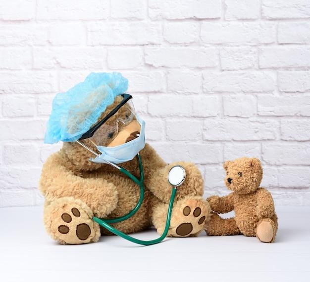 Brauner teddybär sitzt in schützenden plastikgläsern, einer medizinischen einwegmaske und einer blauen kappe, konzept der pädiatrie