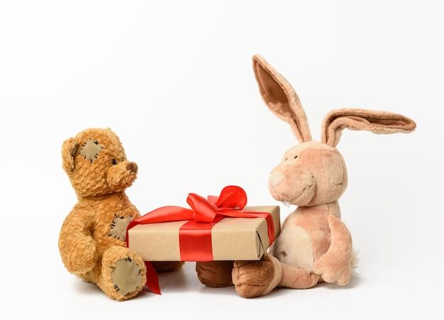 Brauner teddybär und kaninchen halten eine schachtel mit einem geschenk auf weiß
