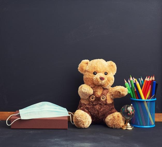 Brauner teddybär und medizinische einwegmaske auf einem schwarzen tafelraum