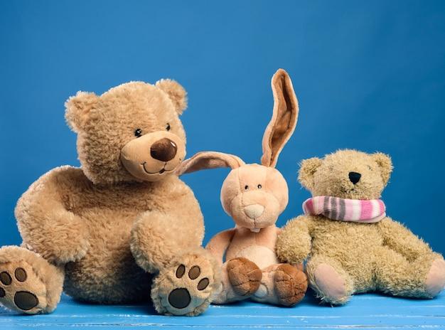 Brauner teddybär und niedliches kaninchen sitzen auf einem blauen hintergrund, freundschaftskonzept