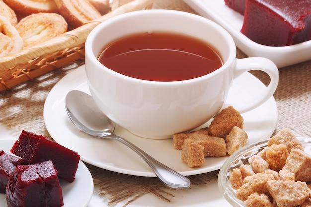Brauner tee mit kirschmarmelade und rohrzucker
