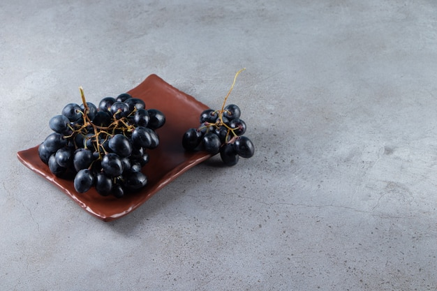 Brauner teller mit frischen schwarzen trauben auf steinhintergrund.