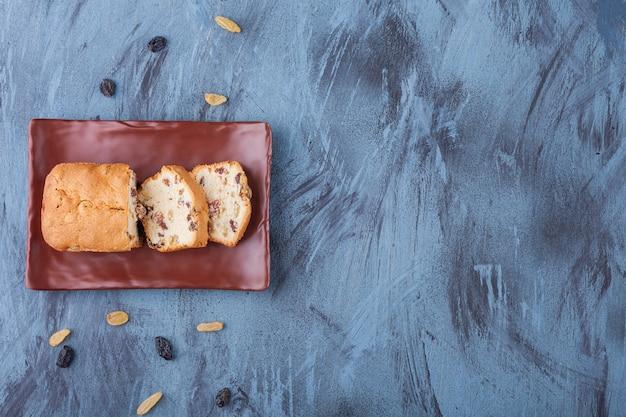 Brauner teller mit geschnittenem rosinenkuchen auf marmoroberfläche.