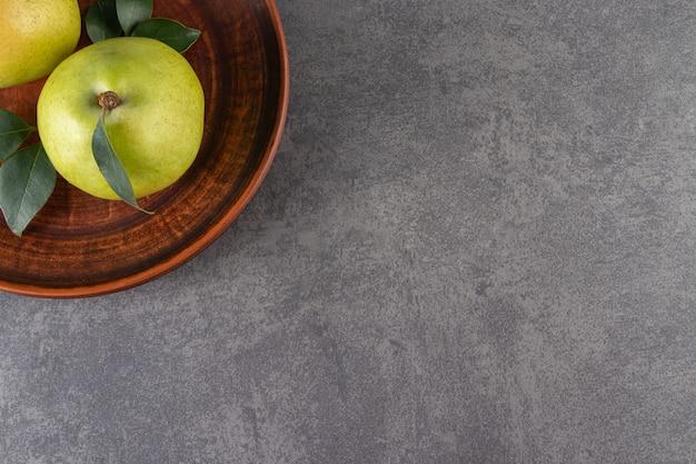 Brauner teller mit grünen äpfeln auf steinoberfläche