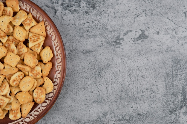 Brauner teller voller trockener gesalzener cracker auf marmor.