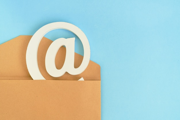 Brauner umschlag mit e-mail am zeichen auf blauem hintergrund