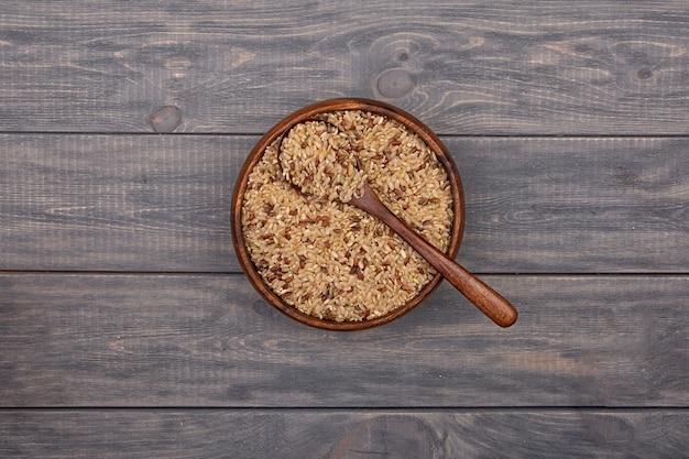 Brauner wildreis in einer hölzernen platte auf einem holztisch. rustikaler stil.