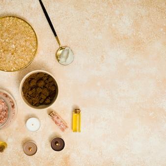 Brauner zucker; kaffeepulver; himalaya-salz und ätherisches öl mit kerzen auf strukturiertem hintergrund