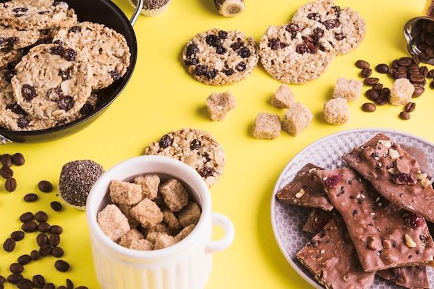 Brauner zucker; kekse; kaffeebohnen und schokoriegel auf gelbem hintergrund