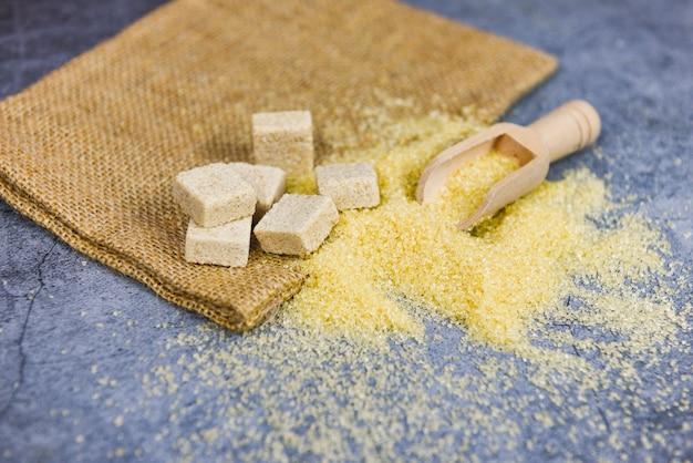Brauner zucker und zuckerwürfel auf dem sack